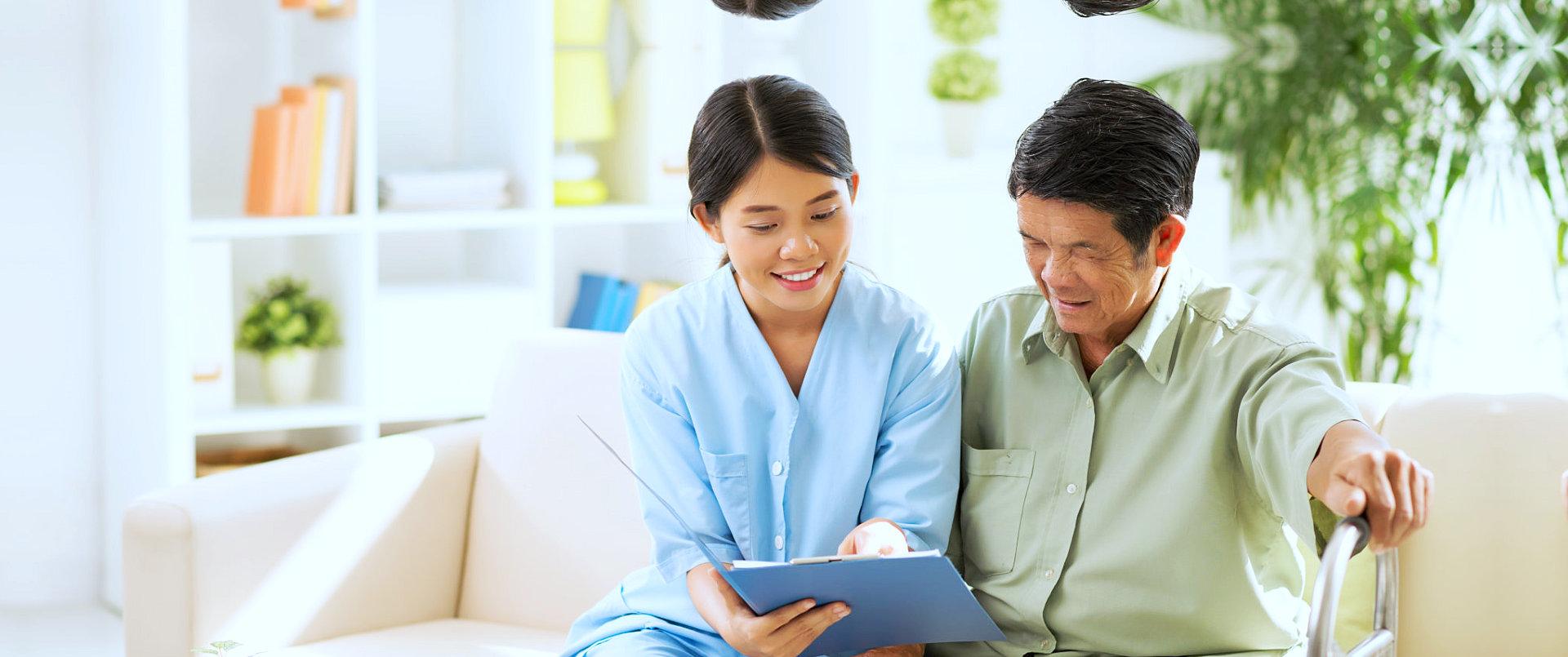 caregiver reading a document for a senior man