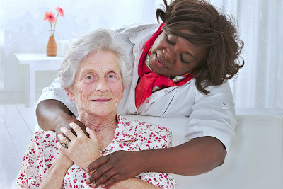 caregiver hugs senior woman smiling