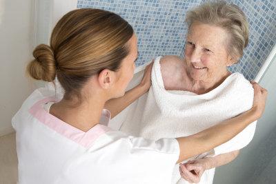 caregiver assisting a senior woman bathing