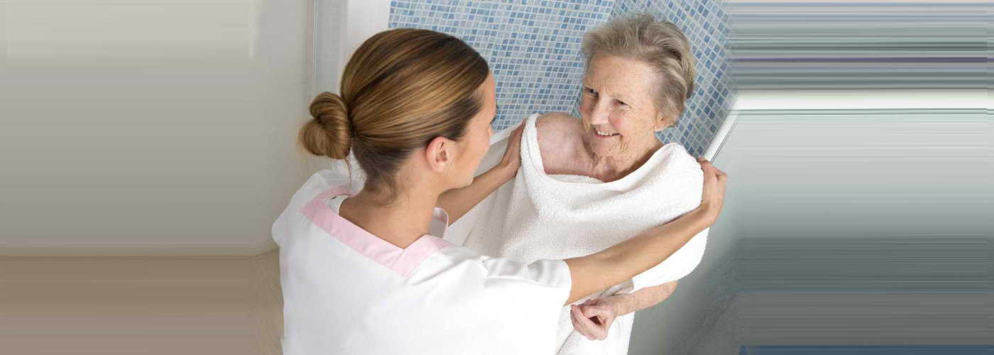 caregiver assisting a senior woman bathing